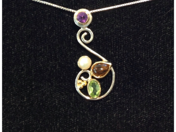 """S"" shape pendant, in sterling silver, accented by bezel set Amber, Peridot and Pearl, with 22KT Vermile accenting around the Gems.  Bail is a slide, under the Round Amethyst, Bezel set With 22KT Vermile Accents.  Designed and Created By Michou."
