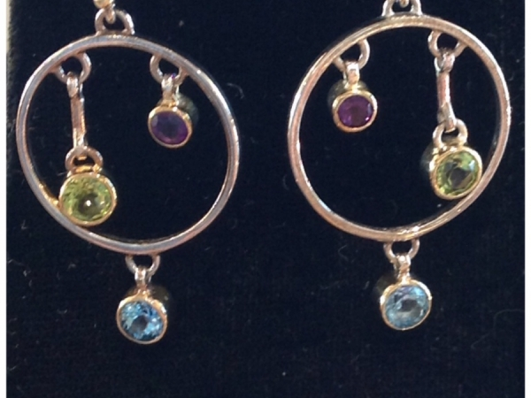 Lady's Two Tone Sterling Silver & 22Kt Gold Vermeil French Hooks, Dangling A Polished Circle Shape, With Two Bezel Set Gems Dangling At Different Heights In The Center Of The Circle; The Peridot And The Amethyst. With A Bezel Set Topaz Dangling From The Bottom Of The Circle Frame. Earrings Designed and Created by MIchou.