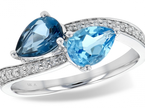 Lady's White 14 Karat Kissing Style Ring, With Two Pear Cut Blue Topaz, One London Blue And One Sky Blue, Each Prong Set With Bulbs Touching In One Place, And Points, Pointing Toward The Shoulders. Each Topaz Is Followed By Hind The Bulb By A Row Of Bead Set Round Diamonds That Continue Half Way Around The Ring.